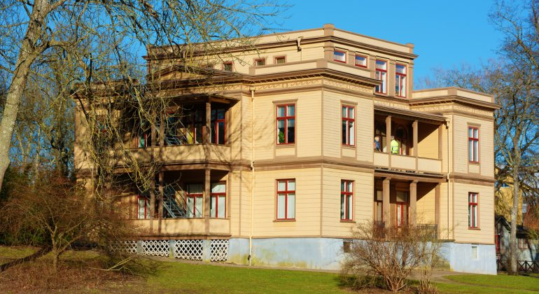 Ronneby, Sweden - February 26, 2016: The Italian villa is a heritage listed building from 1881, built to accommodate rich guests and their servants during spa visits. Two unknown persons on balcony.